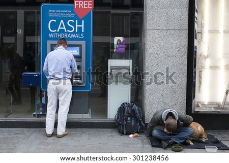 LONDON, UK - JULE 29 2015: Street beggar with dog begging for money near cash mashine. London. UK - stock photo
