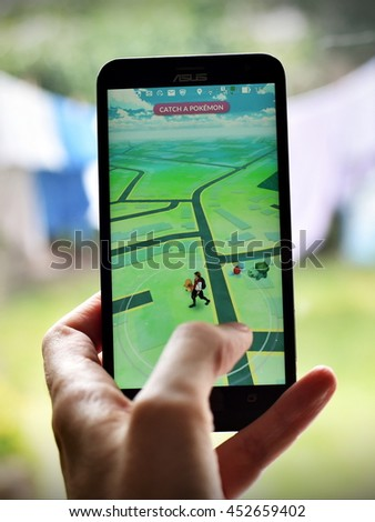 London, UK - July 14, 2016: A gamer uses a smartphone to play Pokemon Go. The worldwide hit Nintendo app has seen been the company's shares increase by 50% with millions of downloads since release. - stock photo