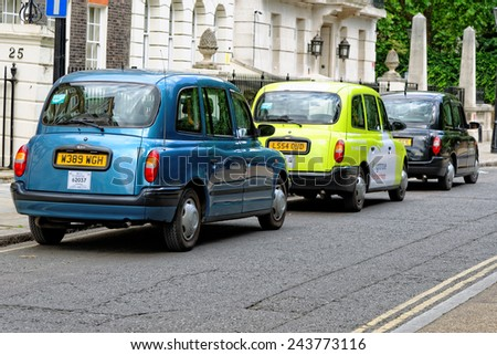 LONDON, UK - JULY 1, 2014: A row of taxis on a central street in London. Motorized hackney cabs in the UK are known as black cabs, although they are now produced in a variety of colours. - stock photo