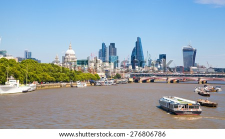 LONDON, UK - 22 JULY, 2014: City of London view from the London bridge. St. Paul cathedral, Lloyds bank, Gherkin, Walkie Talkie building and passing boats on river Thames - stock photo