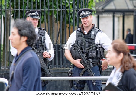 LONDON, UK - JULY 8, 2016: London Metropolitan Police on duty in front ot the House of Parliament. Passing tourists also visible