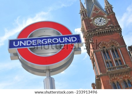 LONDON, UK. JULY 9, 2014: London Underground sign against blue sky and old architecture in central London.