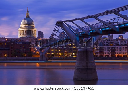 LONDON, UK - JULY 14, 2013: St. Paul's Cathedral and the Millennium Bridge at dusk.