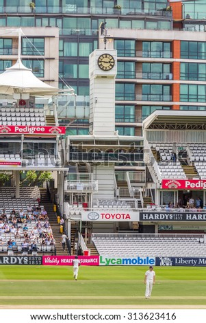 LONDON, UK - JULY 22, 2015: The famous Old Father Time weather vane and clock in the Lord's Cricket Ground in London, UK. It was given by the architect of the Grandstand, Sir Herbert Baker in 1926. - stock photo