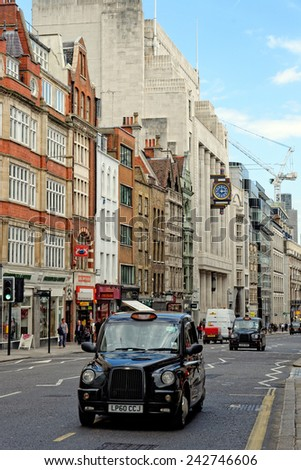 LONDON, UK - JULY 1, 2014: The iconic black cab on Fleet street in London. A street in the City of London, which used to be home of British national newspapers until 1980s. - stock photo
