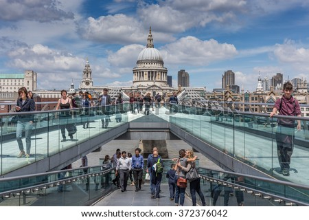 LONDON, UK - JULY 09, 2014: Tourists and commuters walk on the Millennium bridge with St Pauls Cathedral in the background on a sunny summer day