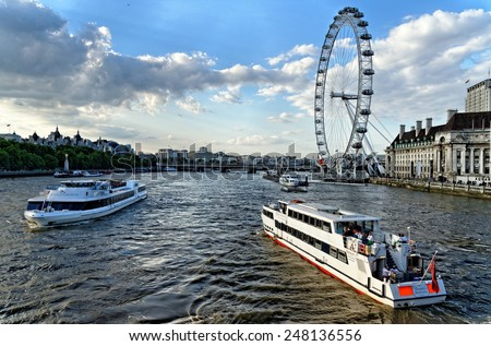 LONDON, UK - JULY 1, 2014: View of Thames river with cruise tour boats near the giant Ferris wheel nicknamed London Eye.Thames is the longest river in England with the length of 346 km. - stock photo