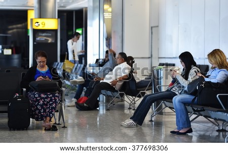 LONDON, UK - JUN 17, 2015: Air travelers wait at a gate at Heahrow Airport. Heathrow is one of the world's busiest airports handling 73.4 million passengers in 2014. - stock photo