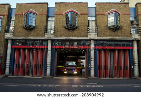 LONDON, UK - JUNE 7, 2014: A fire engine being prepared at Islington Fire Station, London.  The station is part of the London Fire Brigade network of emergency responders. - stock photo