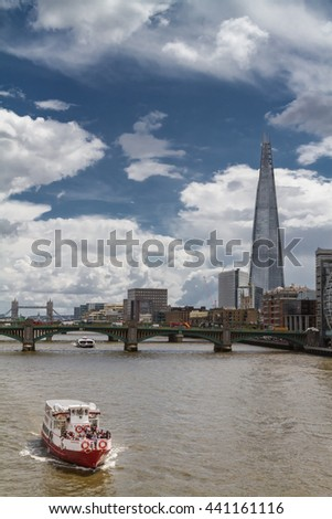 LONDON, UK - JUNE 15, 2016:  A tourist ferry sails on the Thames with The Shard and Tower Bridge in background