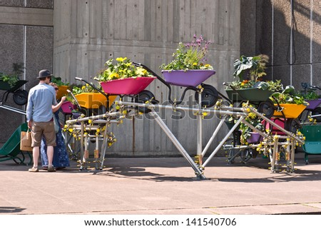LONDON,UK-JUNE 6: An urban wheelbarrow garden is enjoyed by visitors to the Southbank's festival of neighbourhood, that brings urban gardens and allotments to the centre. June 6, 2013 London UK.