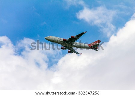 LONDON, UK - JUNE 5, 2015:  Boeing 747 Virgin Atlantic gaining altitude after takeoff  from  London's Heathrow airport. Plane is wearing new livery announced in early 2011.   - stock photo