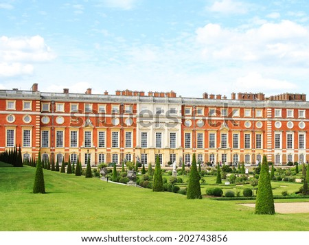 London, UK - 8 June, 2014: Hampton Court Palace, a British royal palace since the reign of Henry VIII, as seen from Hampton Court Palace Gardens on a sunny day. - stock photo