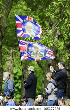 LONDON, UK - JUNE 16: Man holding two Queen's Diamond Jubilee flags during Trooping the Colour ceremony on the Mall and at Buckingham Palace, on June 16, 2012 in London. - stock photo