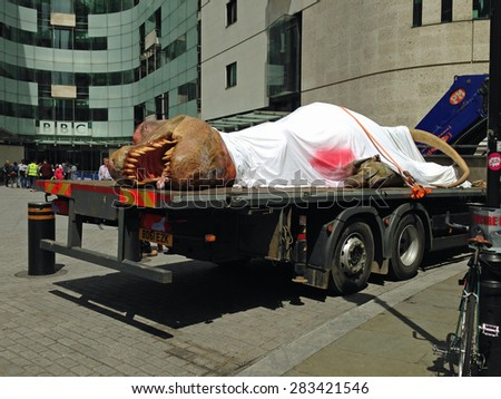 LONDON, UK - JUNE 1, 2015:  National Geographic Channel publicity for its T-Rex Autopsy programme.  Life size tyrannosaurus dinosaur outside BBC Broadcasting House in Portland Place, London. - stock photo