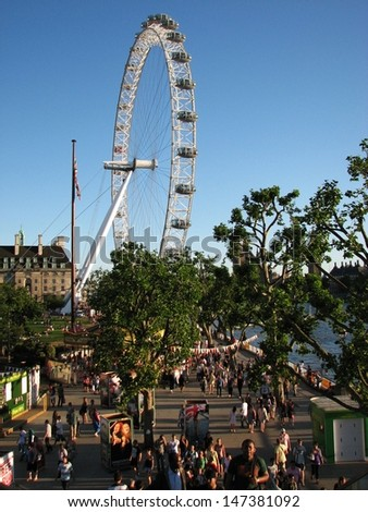 LONDON, UK - JUNE 26: People visit attractions by Thames river on sunny day on June 26, 2011 in London, UK. The London Eye is the most popular paid tourist attraction in the UK. - stock photo