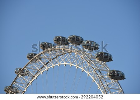 LONDON, UK - JUNE 30 2015: Tourists enjoy the view over the city in the London Eye capsules, Europe's tallest Ferris wheel on the South Bank of the River Thames, a famous tourist attraction - stock photo