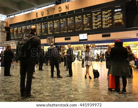 LONDON, UK,  JUNE 1, 2016:  Travelers watching the information departure boards for their gate number at the Euston Railway Station. - stock photo