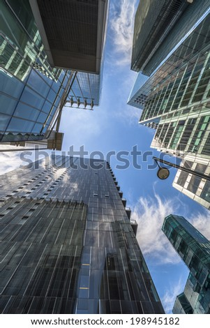 LONDON, UK - JUNE 08, 2014: Upward view of  modern skyscrapers in the City of London, the heart of financial district in London. Over 300,000 people work there, mainly in the financial services sector - stock photo