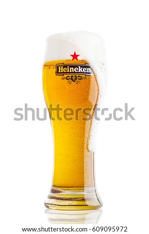 LONDON,UK - MARCH 23, 2017 : A Glass of Heineken Lager Beer on white background with foam. Heineken Lager Beer is a pale lager beer produced by the Dutch brewing company Heineken International