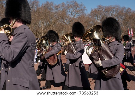 LONDON, UK - MARCH 19: Members of the Queen's Guard  band playing their instruments and marching into Buckingham Palace. March 19, 2011 in London UK. - stock photo