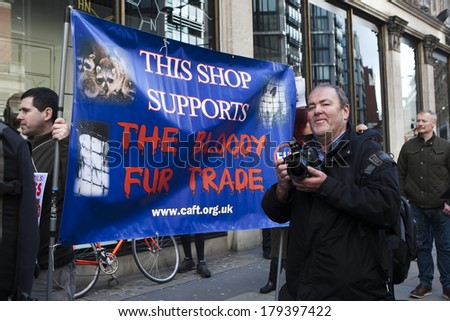 LONDON, UK - MARCH 1TH 2014. Protesting against the fur trade outside Harvey Nichols. written on a poster: This shop supports the bloody fur trade.  In London on 1th March 2014. - stock photo