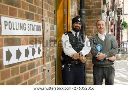 LONDON, UK - MAY 7, 2015:  A policeman and a teller from the Conservative Party outside the polling station in the Fitzrovia Community Centre in Westminster for the General Election.