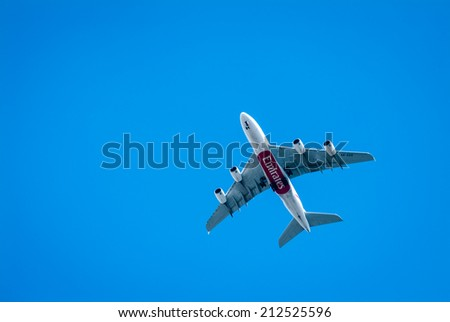 LONDON, UK - MAY 25, 2014: An Emirates plane flying in clear blue sky over London. - stock photo