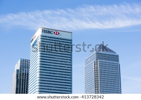 LONDON, UK - MAY 1, 2016: Cropped shot of Canary Wharf HSBC bank building next to skyscrapers against blue sky. Canary Wharf is London's second financial district. - stock photo