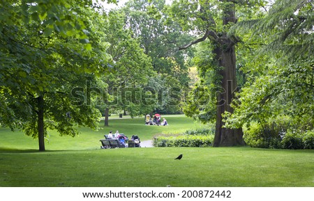 LONDON UK - MAY 15, 2014: Old English park south of London. Young mother and child resting on grass
