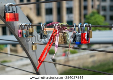LONDON, UK- MAY 3, 2014: Padlocks attached to the Millennium Bridge as a symbol of a couples love in London on May 3rd, 2014. - stock photo