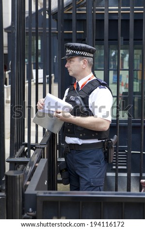LONDON, UK - MAY 14, 2014: - Policemen on duty, Security officers in front of PM's residence at Downing Street 10. Parliament street in London, the address for ministries and government institutes  - stock photo