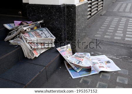 London, UK - May 25, 2014: Tabloid newspapers in a shop doorway on May 25, 2014. Headlines in the Daily Mirror report on the four sailors lost at sea when their yacht ran into trouble in the Atlantic. - stock photo
