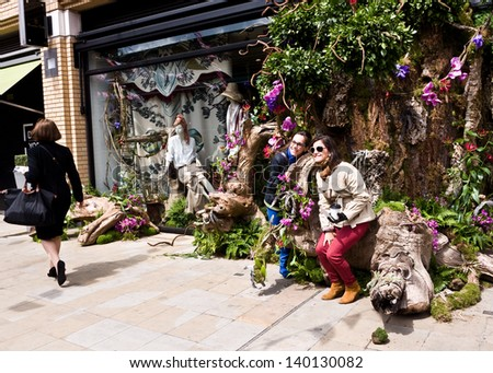 LONDON, UK-MAY 26: Visitors enjoy designer Massimo Dutti's Store decked out with exotic plants,  as part of the Chelsea Fringe celebrating 100 years of the Chelsea Flower Show. May 26, 2013 London UK. - stock photo