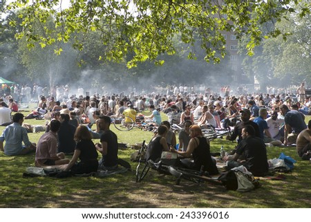 LONDON, UK - MAY 30: Young people are fried kebabs and rest in a local park in Hackney on May 30, 2014 in London, UK. - stock photo