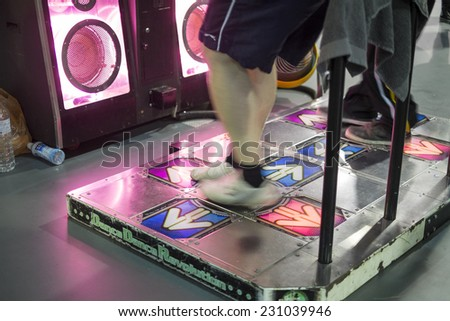 LONDON UK - NOVEMBER 15: Legs of participants playing dancing video game in Hyper Japan. November 15, 2014 in London. Held in Kensington Olympia this year, the event celebrates all things Japanese. - stock photo