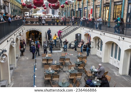LONDON, UK - NOVEMBER 5, 2014 : Musical string band busking under the lights and Christmas decorations hanging from the roof in the Apple Market at Covent Garden in central London.