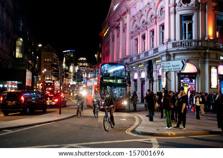 LONDON, UK - OCT 4: People stroll in Piccadilly on a Friday night in London on October 4, 2013. From pubs to upmarket bars, nightclubs and late night shopping, Piccadilly is a popular nightlife area. - stock photo