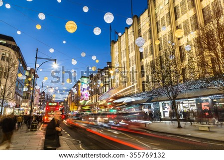 LONDON, UK - 23RD DECEMBER 2015: A view of Oxford Street during the Christmas Season showing buildings, decorations, people and traffic.