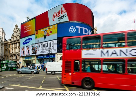 LONDON, UK - SEPTEMBER 26, 2014: A double decker bus and cars passing Piccadilly Circus with its neon signage advertising for companies like Coca Cola, TDK, Vogue, Samsung and Mc Donalds on September - stock photo