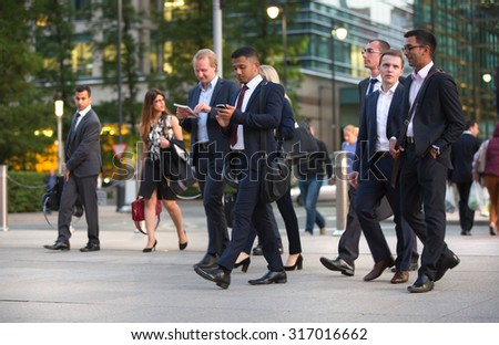 LONDON, UK - 7 SEPTEMBER, 2015: Canary Wharf business life. Group of business people going home after working day. - stock photo