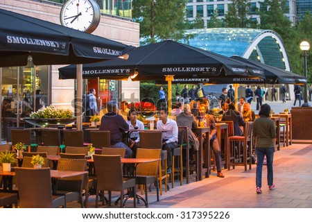 LONDON, UK - 7 SEPTEMBER, 2015: Canary Wharf night life. People sitting in local restaurant after long hours working day - stock photo