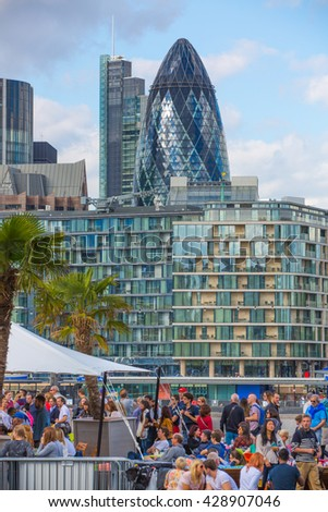 London, UK - SEPTEMBER 19, 2016: City of London view from the river Thames. International business and banking aria. View include Gherkin building and lots of pelops in cafe