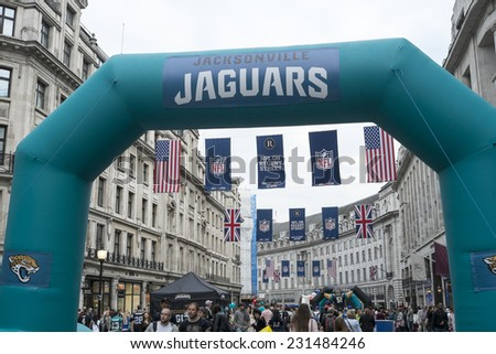 LONDON UK - SEPTEMBER 27: Crowded Regent street with Jaguars inflatable arch and NFL flags above. September 27 2014 in London. The street was closed to traffic to host NFL related games and events. - stock photo