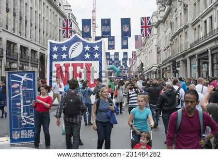 LONDON UK - SEPTEMBER 27: Crowded Regent street with NFL inflatable banners and flags hanging above. September 27 2014 in London. The street was closed to traffic to host NFL related games and events. - stock photo