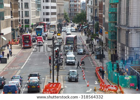LONDON, UK - SEPTEMBER 19, 2015: Holborn street with traffic and people crossing the road - stock photo