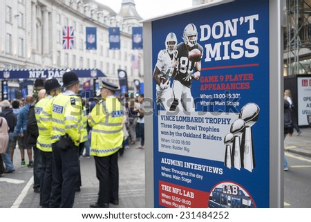 LONDON, UK - SEPTEMBER 27: NFL billboard with British policemen standing in the background. September 27, 2014 in London. Regent street was closed to traffic to host NFL related games and events. - stock photo
