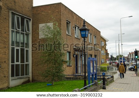 LONDON, UK - SEPTEMBER 5, 2015: Pedestrians and motorists passing the  Metropolitan Police station in Dagenham, East London on a cloudy Saturday in early September. - stock photo