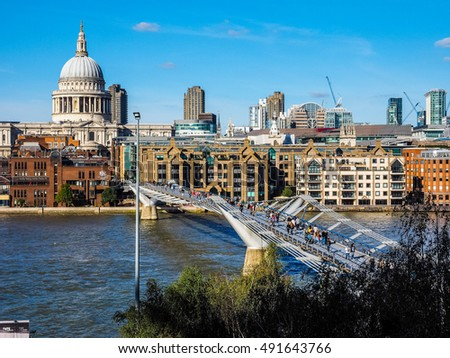 LONDON, UK - SEPTEMBER 28, 2015: People crossing the Millennium Bridge over River Thames linking the City of London with the South Bank between St Paul Cathedral and Tate Modern art gallery (HDR)