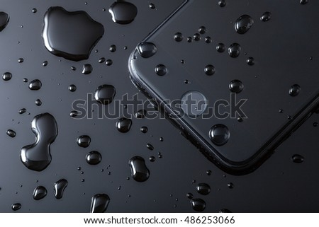 London, UK - 20 September 2016: The Apple iPhone 7 launched this week with water resistance. This image shows a close up of the home button on the front of a black iPhone 7 with drops of water.